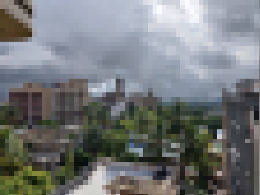 A heavily-pixelated view from my home. Looks out into the cloudy sky, covering the top half of the image. The bottom half features tall building both close and far away, as well as lush green trees between the farther and nearer buildings.
